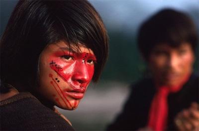 Молодой индеец расписанный красителем аннато
